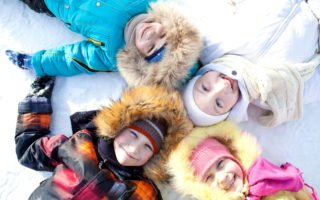Joyful children lie on their backs on a winter outing